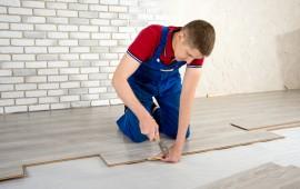 Young handsome men laid laminate floor covering, perform repairs